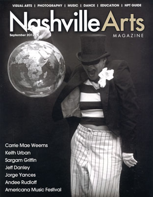 Carries work on the         cover of Nashville Arts magazine features person in top hat and mask holding a blow up globe